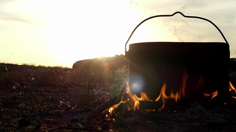 Big cauldron stands in a campfire. It boils hot water at sunset in slow motion Footage