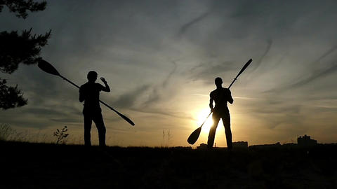 Two men are fighting with two paddles at sunset in slo-mo Footage