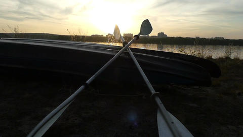 Two oars lie on a catamaran boat on a lake bank at sunset Image