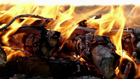 A closeup of a campfire with bright forks of flame at night in slow motion Footage