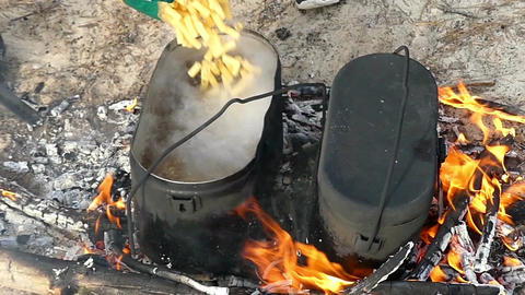 Two dark cauldrons with boiling watet on fire place in slow motion Footage