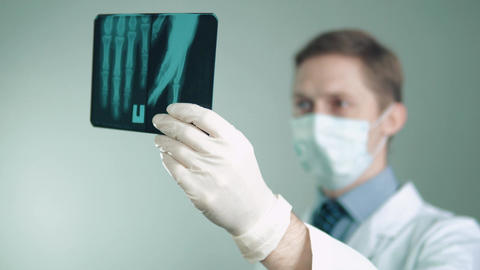 Doctor in mask and gloves looks at X-ray Live Action