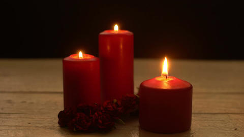 Three red candles light with roses romantic theme Stock Video Footage