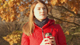 Happy Smiling Woman Enjoying Nature. Young female in red coat with hot mug ビデオ