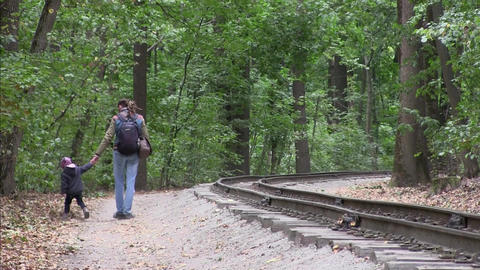 Father and daughter walk in forest along the railway in autumn Filmmaterial