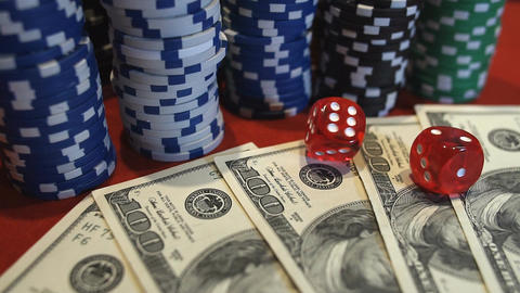 Red dice falling on money, gambler playing game at casino, addiction to gambling Footage