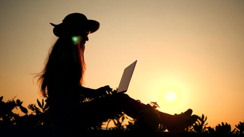 Young Woman Working on Laptop Silhouette Against Beautiful Beach Sunset on Footage