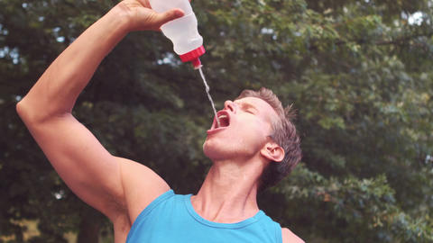 Handsome athlete drinking water out of bottle Footage
