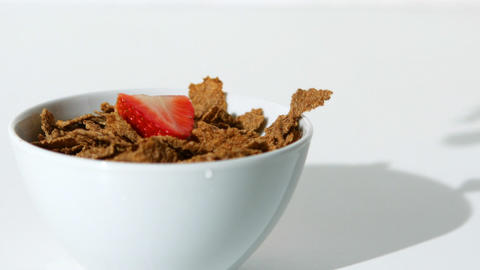 Strawberries falling in a wheat cereals bowl Footage