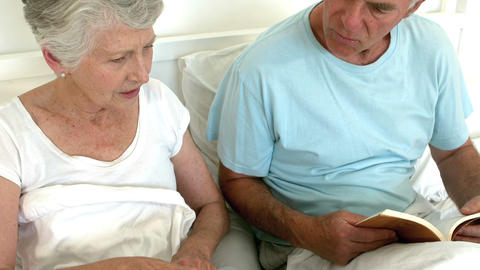 Senior couple reading book and using laptop Footage