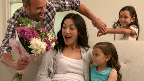 Father and daughter giving bouquet to mother Footage