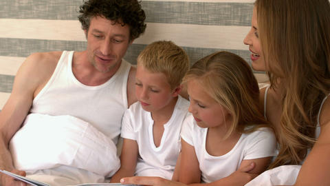Cute family reading a book on their bed Footage