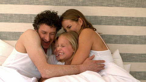 Cute family hugging on their bed Footage