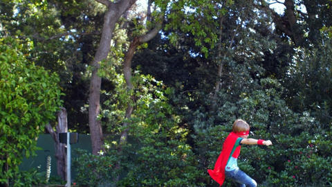 Cute boy playing super hero in the garden Footage