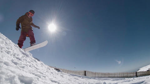 Snowboarder jumping against blue sky Footage