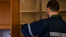 Man looking in cupboard for pest control Footage