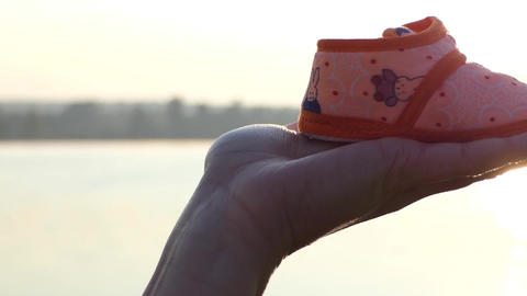 a Pregnant Woman Keeps Slippers For Her Baby on Her Hand at Sunset in Autumn Live Action