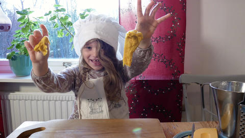 A happy girl plays with the dough Live Action