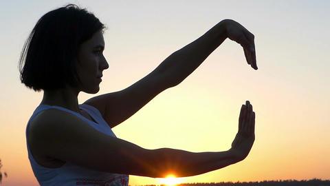 a Cheery Slim Woman Does Waving Movements With Her Hands at Sunset in Slo-Mo Footage