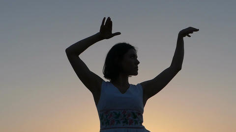 a Young Slim Woman Does Dancing Movements With Her Hands at Sunset in Slo-Mo Live Action
