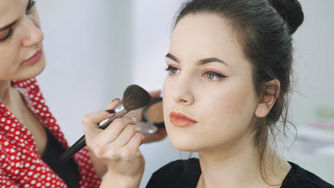 Master makes make-up of young girl in beauty salon Foto