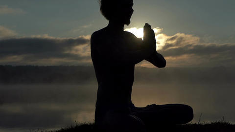 Spiritual man sits on a lake bank and practices yoga at sunset in slow motion Live Action