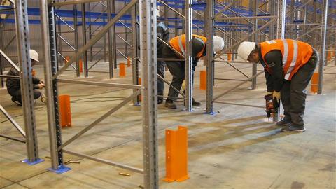 Motion around Workers Group Assembling Metal Racks Footage