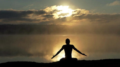 Spiritual yogi sits in lotus on a lake bank and prays at sunset in slow motion Live Action