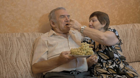 An elderly woman feeds her husband's grapes. They are a happy couple Footage