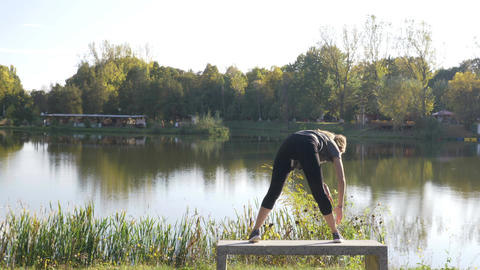Attractive young girl inhaling and exhaling doing yoga stretches in a park on a Footage
