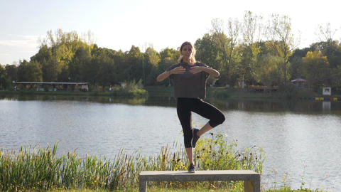 Young slim woman meditating and doing yoga poses standing on one leg in a park Footage