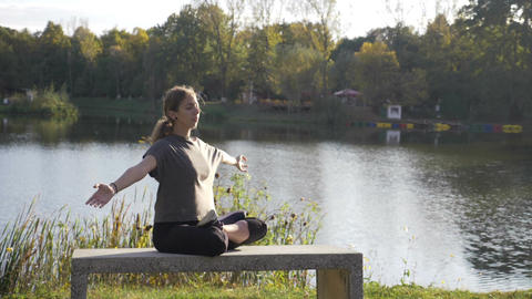 Young adult female practicing yoga in lotus position and having her hands in Footage