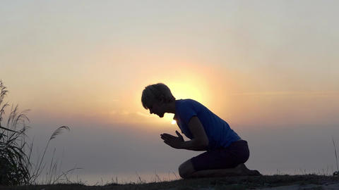 Young man kneels and prays on a lake bank at sunset in slo-mo Footage