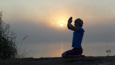 Young man sits and prays on a lake bank at sunset in slo-mo Footage