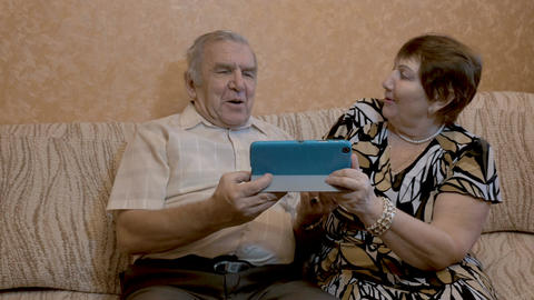 An adult couple uses a tablet, they sit on the couch Footage