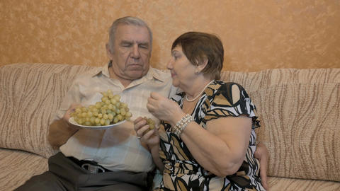 Elderly couple eating grape berries Footage