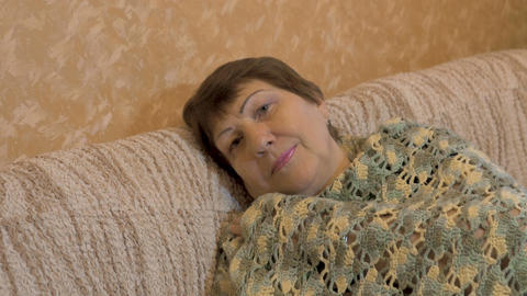 Portrait of happy elderly woman. She is resting on the couch Footage