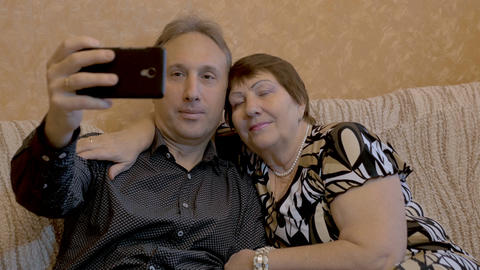 An elderly woman and her adult son are photographed on a smartphone Footage