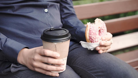Woman bites donut and drinking coffee Archivo