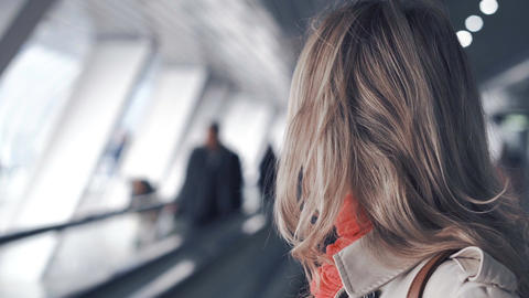 Young blond woman is riding on the travelator Archivo