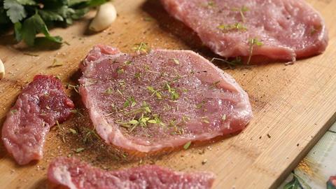 Sprinkling green thyme over pork slices Footage