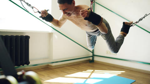Young man doing exircise on quartering yoga equipment and pull his arms and legs Fotografía