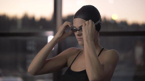 Woman swimmer putting goggles on face for underwater swimming in pool Footage