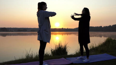 Two Women Put Hands Aside While Doing Yoga at Sunset on a Lake Coast in Slo-Mo Footage