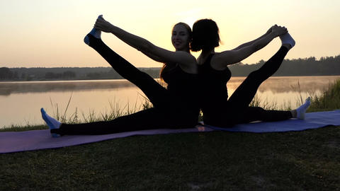 Two Young Women Practice Yoga Sitting on Mats Back-To-Back at Sunset in Slo-Mo Footage