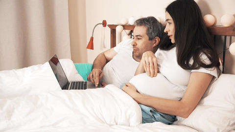 Man and his beautiful pregnant wife using their laptop in their bed Footage