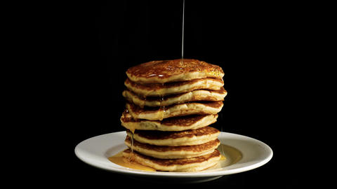 Syrup flows down on a pile of pancakes Footage