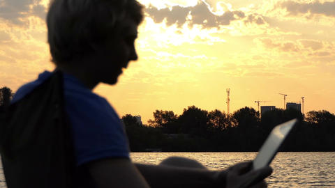 Man Sits on a Folding Chair And Looks at His Tablet pc at Sunset out of focus Footage