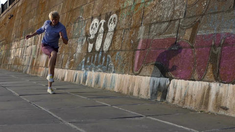 Young Man Dances Disco on a Riverbank With a High Stone Wall in Summer in Slo-Mo Footage