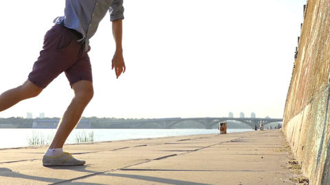 Male Legs Dance Disco on a Riverbank With a High Stone Wall in Summer in Slo-Mo Footage